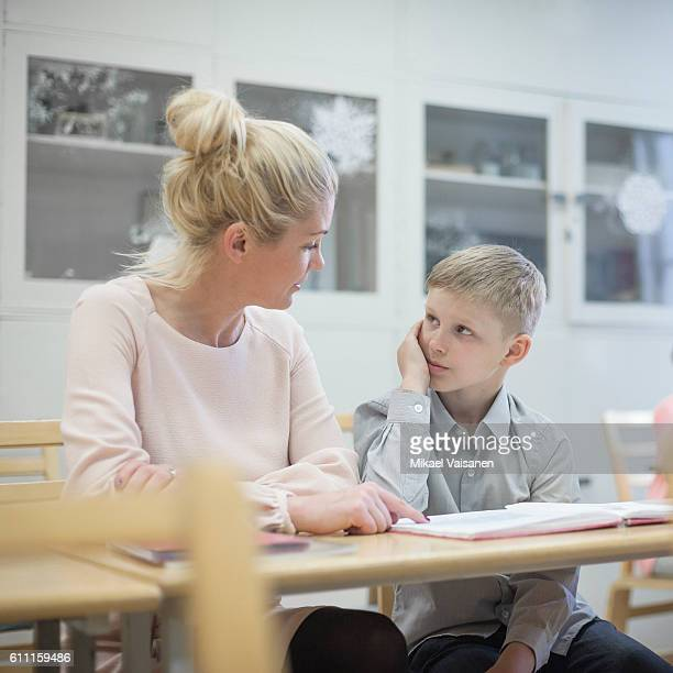 Young pupil studying with teacher at school desk