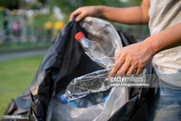 young pupil wearing jeans and sneakers gathering empty bottles in the forest - campaigner stock pictures, royalty-free photos & images
