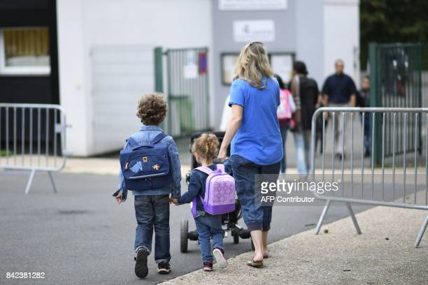 Young pupils and their mother arrive at their primary school at the start of the new school year on September 4 in CorbeilEssonnes outside Paris /...