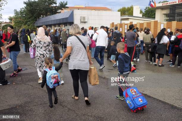Young pupils arrive with their parents at the Bessieres Jean Zay Marie Curie primary school at the start of the new school year on September 4 in...