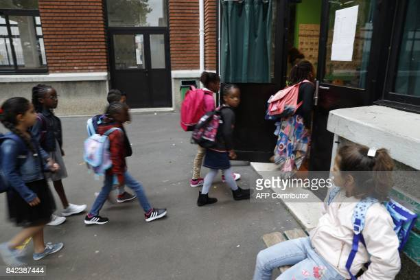 Young pupils enter in a classroom at the Bessieres primary school at the start of the new school year on September 4 in the 17th arrondissement in...