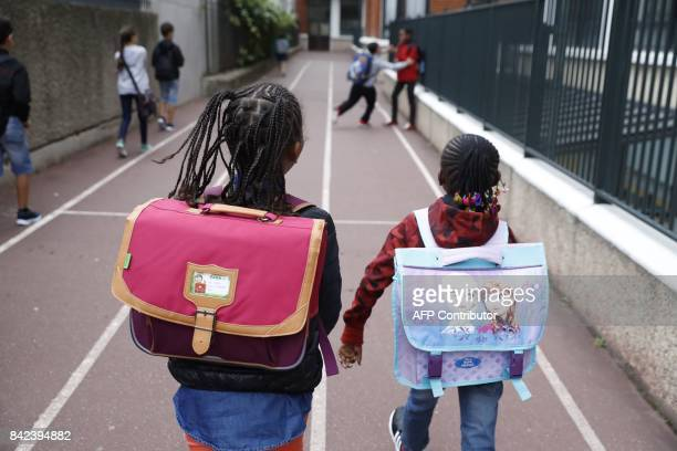 Young pupils walk at the Bessieres primary school at the start of the new school year on September 4 in the 17th arrondissement in Paris / AFP PHOTO...