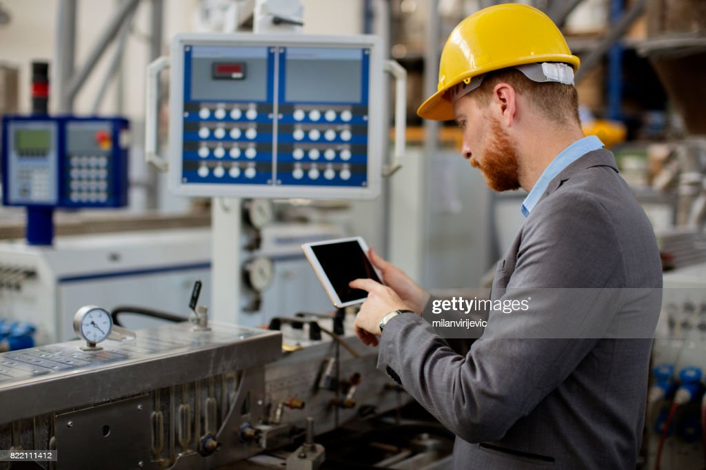 Young quality inspector checking factory work : Stock Photo
