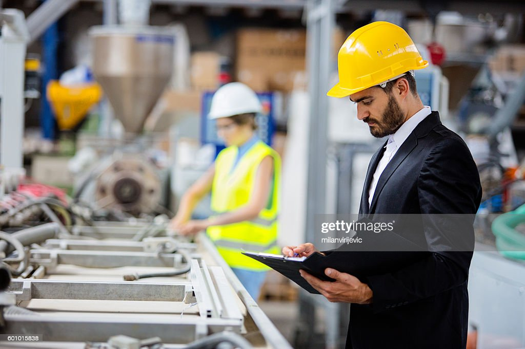 Young quality inspector checking production line : Stock Photo