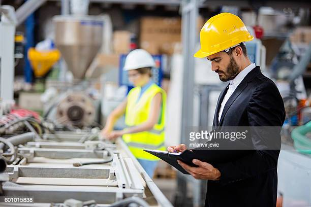 young quality inspector checking production line - inspector stock pictures, royalty-free photos & images