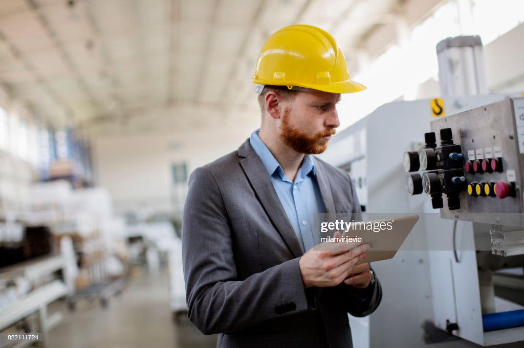 Young quality inspector in factory : Stock Photo