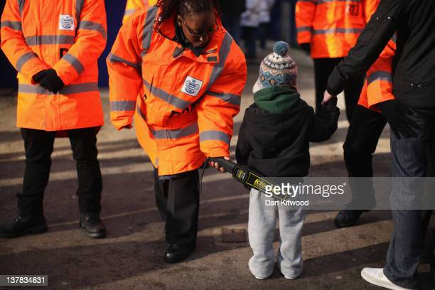 A young Queen's Park Rangers fan is searched with metal detector before entering the family stand at the Loftus Road stadium on January 28 2012 in...