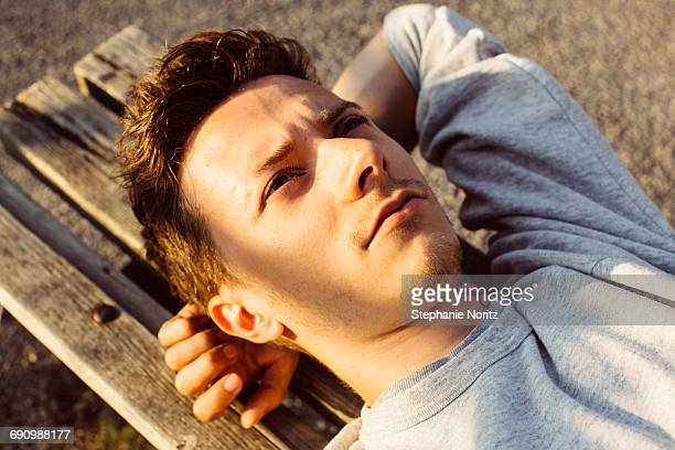 Young queer man laying on park bench looking up