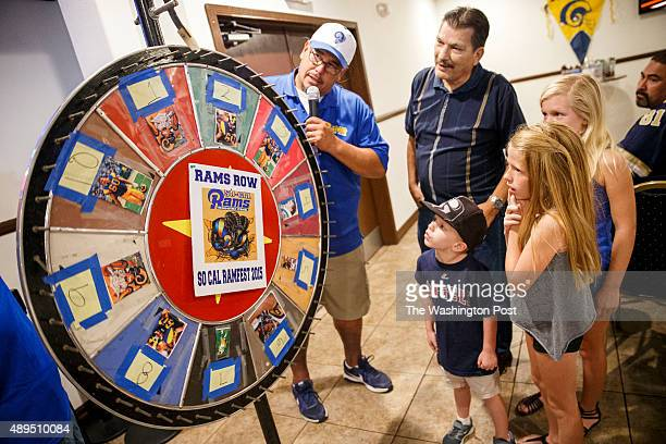 Young Rams fans spin a wheel to win a raffle prize during halftime as Rams Fans with the Southern California Rams Booster Club watch the NFL football...