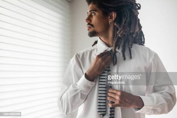 Young rasta man getting dressed for an interview putting on a tie while looking away