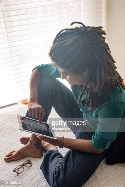 Young rasta man looking at his social media while sitting down on floor at home smiling