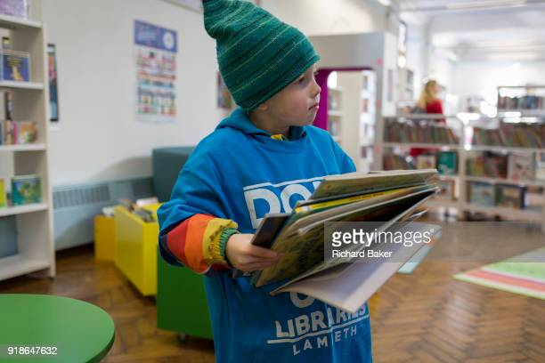 A young reader collects books to borrow in the reopened Carnegie Library on Herne Hill in south London which has opened its doors for the first time...