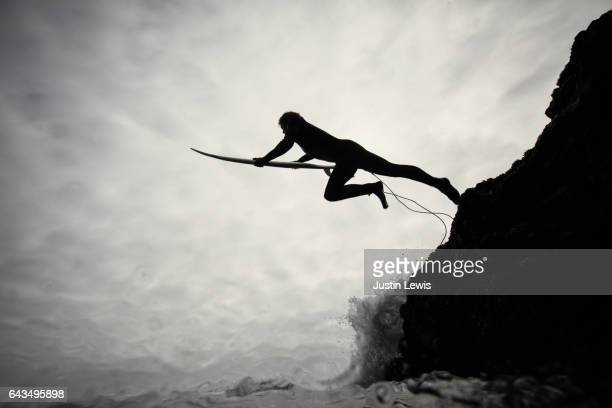 """young """"real people"""" surfer plunges off cliff into ocean on cloudy sky morning in california - taking the plunge stock photos and pictures"""