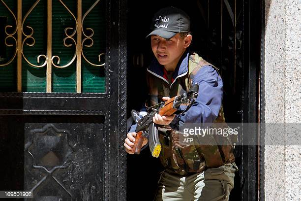 A young rebel fighter holds a weapon standing at the entrance of a house on March 29 2013 in the Sheikh Maqsoud neighbourhood of the Syrian city of...