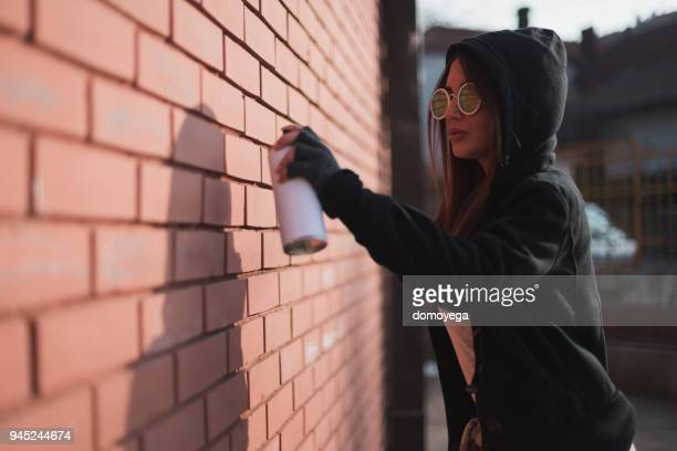 young rebel writing graffiti on the wall with a spray bottle - street artist stock pictures, royalty-free photos & images
