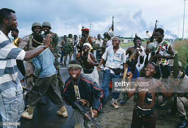 Young rebels pose and display their weapons as they chat with ECOMOG soldiers in Monrovia during the Liberian Civil War In 1989 Charles Taylor leader...