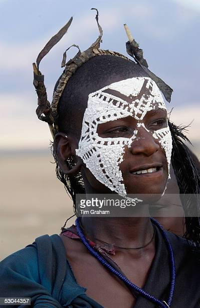 Young recently circumcised Masai Warrior with traditional face paint after 'coming of age' in the Serengei Plains Tanzania