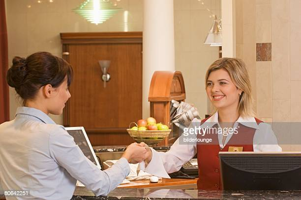 young receptionist handing out key card to female hotel guest