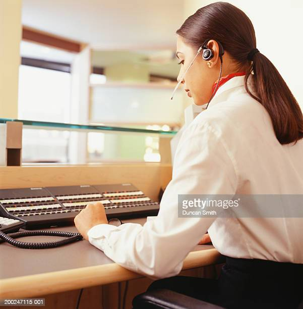 Young receptionist wearing headset, using switchboard