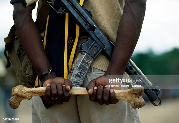 A young recruit for the National Patriotic Front of Liberia grasps a human leg bone while at a training camp in Gborplay Liberia Responding to years...