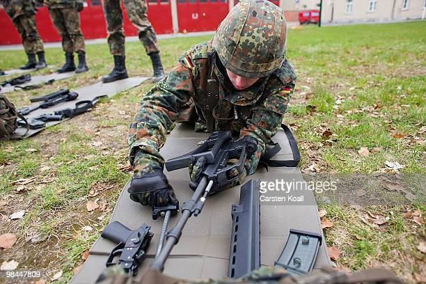 A young recruit of the Bundeswehr guard of honour fragments the G36 assault rifle during a basic training at the Julius Leber barracks on April 14...