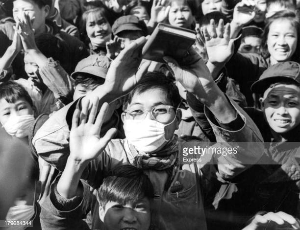 Young Red Guards acclaim the thought of Mao One boy wears a mask as he waves his book of Mao's Thoughts in Beijing China