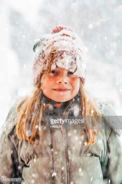 jong rood harig meisje dat van de sneeuw geniet die in openlucht speelt - seizoen stockfoto's en -beelden