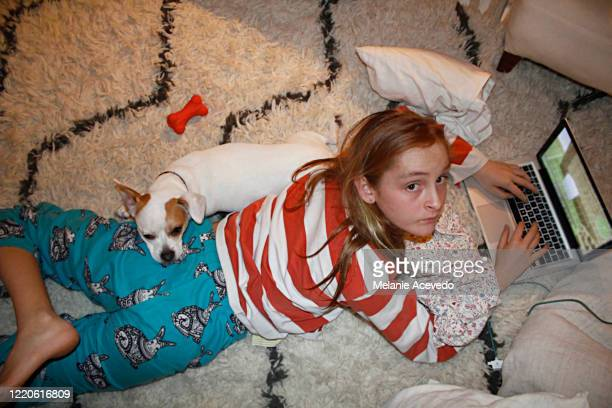 young red headed girl short hair brown eyes and freckles using laptop on carpet floor looking up at camera dog is resting on her back both looking up at camera