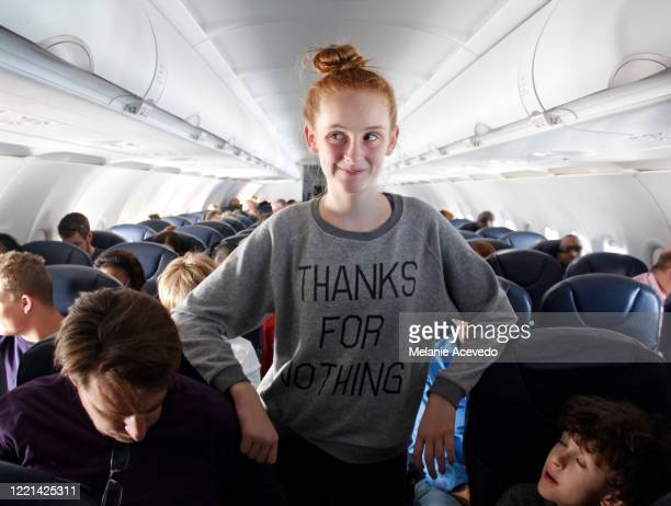 a young red headed girl with brown eyes and freckles standing in the middle aisle of an airplane. she is wearing a sweatshirt with a funny saying , leaning on the seats next to her on her elbows and making a funny face. - jeune fille rousse photos et images de collection