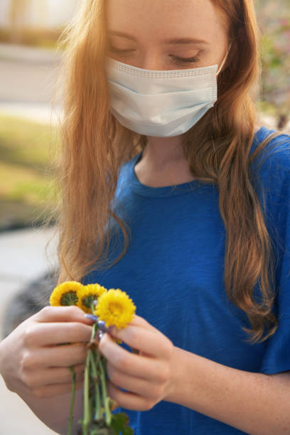 Young red-haired woman wearing a protective face mask holding dandelions