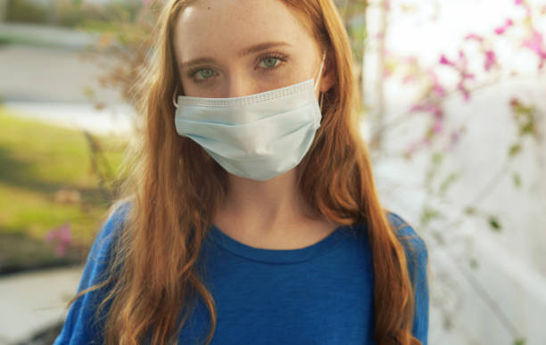 Young red-haired woman wearing a protective face mask next to her house