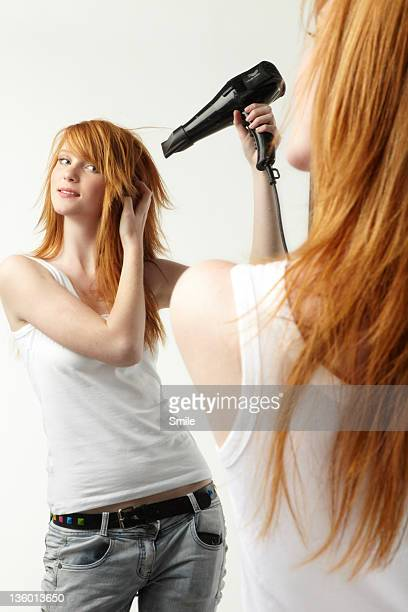 Young redhead blowdrying her hair in the mirror