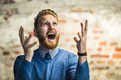 Young redhead businessman shouting from frustration.