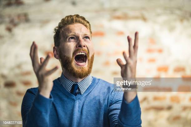 young redhead businessman shouting from frustration. - fury stock pictures, royalty-free photos & images