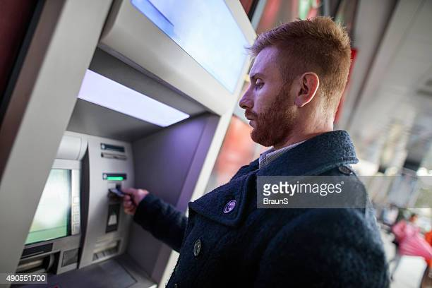 young redhead businessman withdrawing money from atm machine. - ginger banks stock pictures, royalty-free photos & images