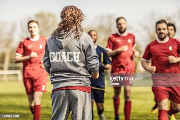 young redhead female soccer coach with her male football team - coach stock pictures, royalty-free photos & images