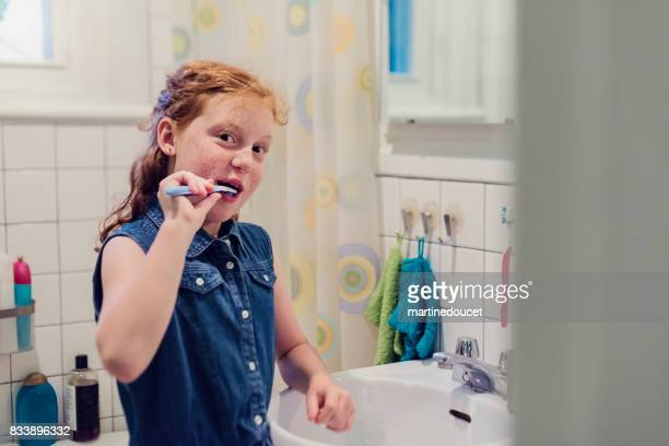 Young redhead girl brushing teeth on school morning.