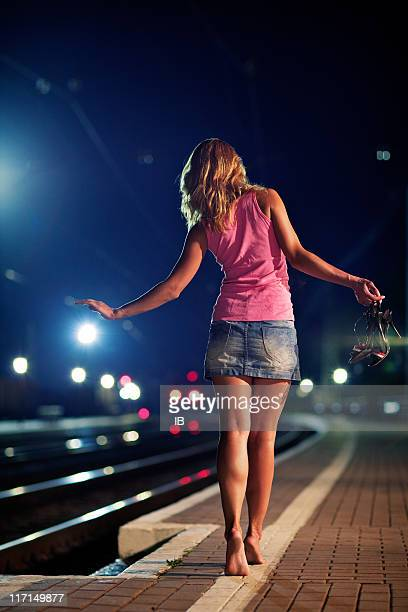 Young redhead girl goes tiptoe on the railway platform