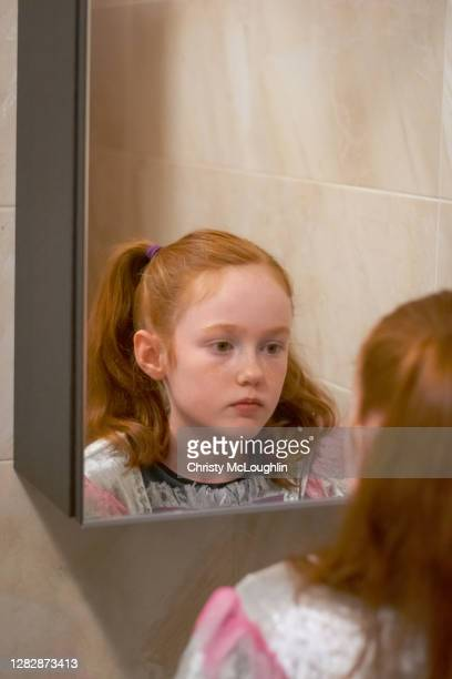a young redhead girl looking in mirror with serious expression - looking stock pictures, royalty-free photos & images