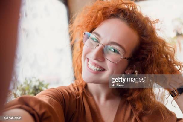 junge rothaarige nehmen selfie auf smartphone - junge frau allein fotos stock-fotos und bilder