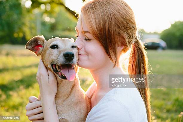 young redhead woman hug her small mixed-breed dog - redhead girl stock photos and pictures