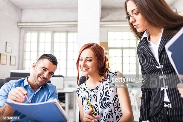 Young redhead woman signing papers in modern office