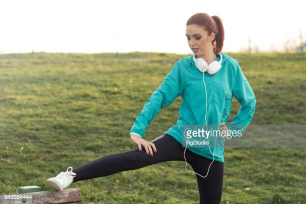 young redhead woman stretching after training - hoodie headphones stock pictures, royalty-free photos & images