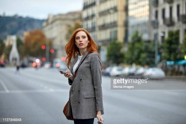 young redhead woman walking with mobile phone - grey blazer stock pictures, royalty-free photos & images