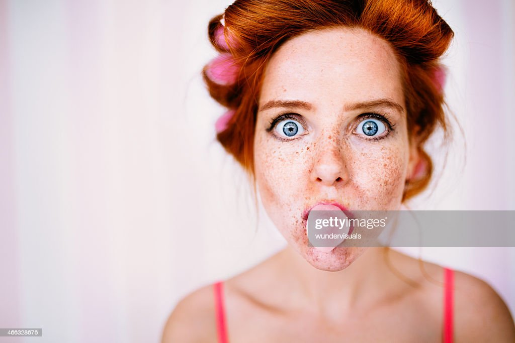Young Redhead Woman With Curlers In Hair Blows Bubble : Stock Photo