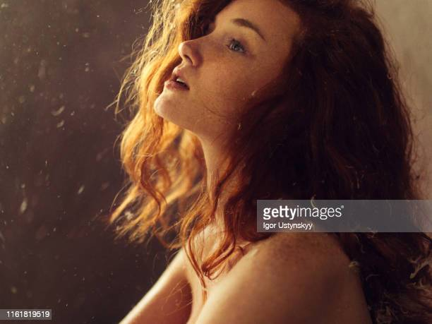young redhead woman with feathers falling around - junge frau rätsel stock-fotos und bilder
