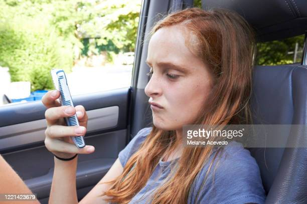 young redheaded girl brown eyes and freckles sitting in passenger seat using cellphone not looking at the camera feet up on the dashboard typing on phone close up putng and scrunching face together