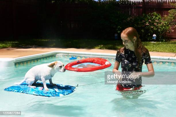 young redheaded girl brown eyes and freckles standing up in pool looking at dog who is standing on boogie board girl is smiling and pushing the string of boogy board wearing swim shirt wet hair