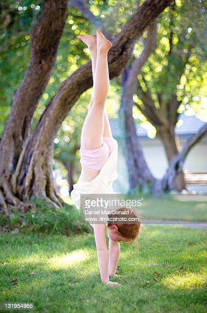 young redheaded girl doing handstand - girl in dress doing handstand stock photos and pictures