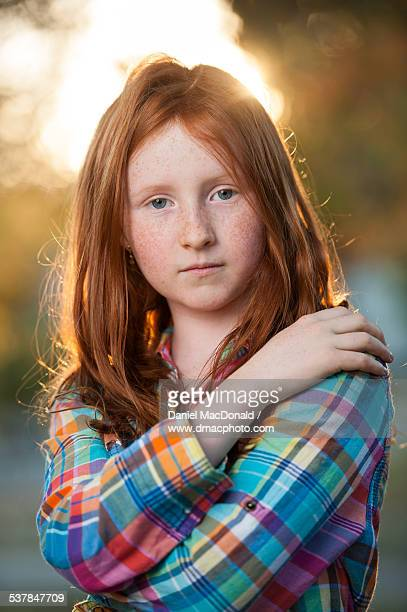 Young redheaded girl in plaid shirt in autumn